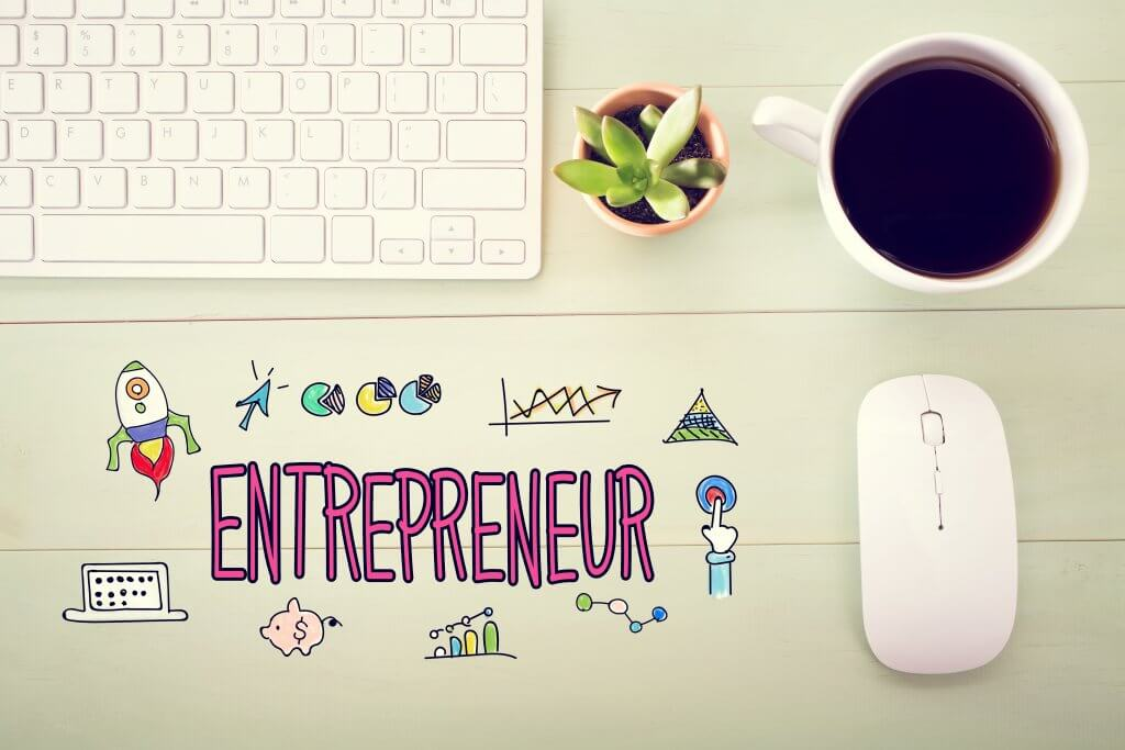 Image - Entrepreneur concept illustration with workstation on a wooden desk, with a keyboard, plant and coffee
