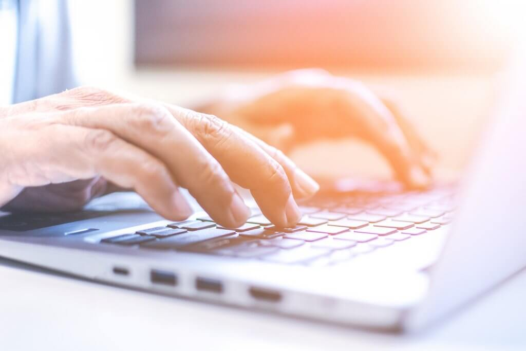Image - hands typing on laptop, with a sun glare overlay